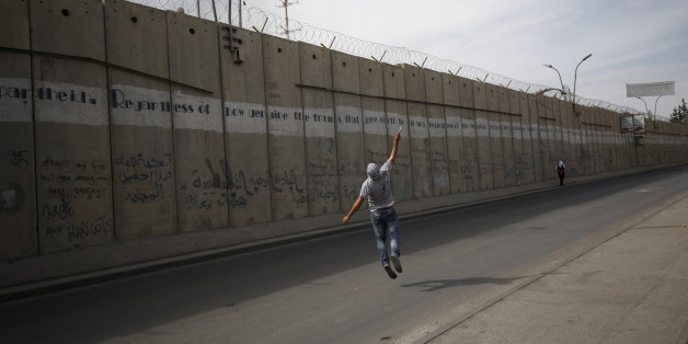 A Palestinian protester hurls stones towards Israeli troops taking positions behind the Israeli barrier during clashes in the West Bank town of Al-Ram, near Jerusalem October 22, 2015. Nine Israelis have been killed in Palestinian stabbings, shootings and vehicle attacks since the start of October. Forty-nine Palestinians, including 25 assailants, among them children, have been killed in attacks and during anti-Israeli protests. Among the causes of the turmoil is Palestinians' anger at what they see as Jewish encroachment on the al-Aqsa mosque compound in Jerusalem's walled Old City. REUTERS/Mohamad Torokman