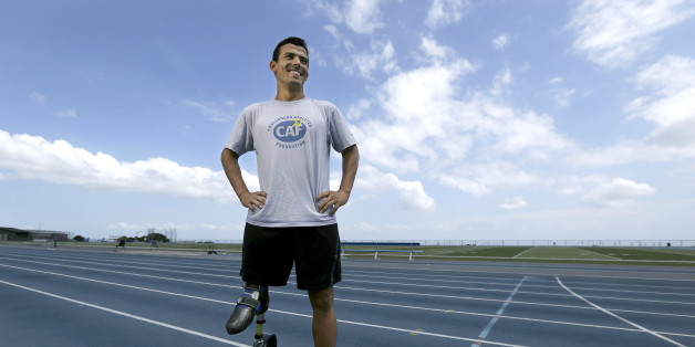 In this May 7, 2013, photo, Mohamed Lahna, a 2016 Paralympic hopeful in the triathlon, poses for a photograph on the College of San Mateo track in San Mateo, Calif. A para-triathlete for all of five years, the 31-year-old native of Morocco has his sights set on the 2016 Paralympics in Rio de Janeiro. Born without a femur in his right leg, Lahna has a tiny foot at about knee level that fits into a prosthetic that goes all the way up to his glute. (AP Photo/Jeff Chiu)