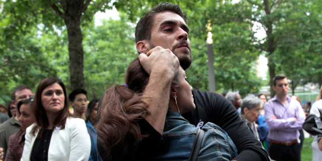A man and woman embrace during a public tribute to the victims of the mass shooting in an Orlando nightclub, at the 911 Memorial at the site of the World Trade Center in Manhattan, New York, U.S., June 16, 2016. REUTERS/Mike Segar  TPX IMAGES OF THE DAY