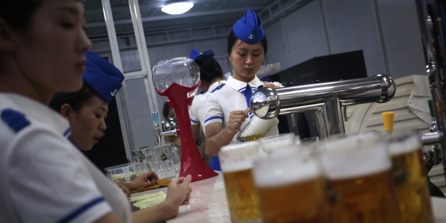 A waitress fill up jugs of beer during Taedonggang Beer Festival in Pyongyang, North Korea, Sunday, Aug. 21, 2016. The festival, the first of its kind in the country, was held as a promotional event for the locally brewed beer. (AP Photo/Dita Alangkara)