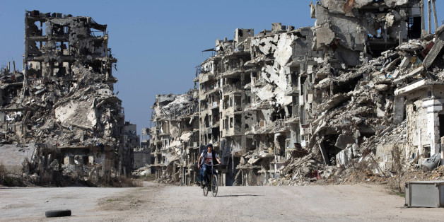 """A Syrian boy rides a bicycle through a devastated part of the old city of Homs, Syria, Friday, Feb. 26, 2016. The U.N. Security Council is expected to vote Friday afternoon on a draft resolution endorsing the """"cessation of hostilities"""" in Syria that is set to start at midnight local time. The draft, obtained by The Associated Press, also urges the U.N. secretary-general to resume Syria peace talks """"as soon as possible."""" (AP Photo/Hassan Ammar)"""