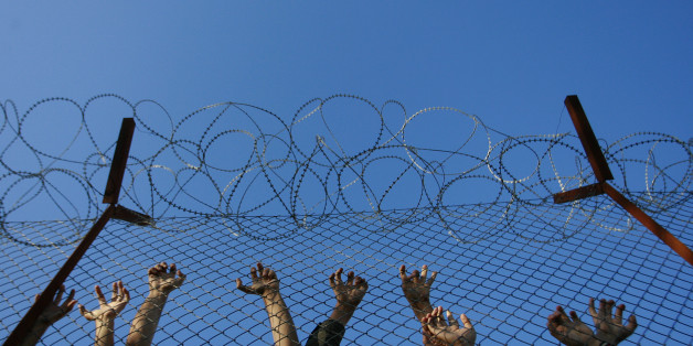 Immigrants lean on fences during unrest inside Pagani detention centre, in the eastern Aegean island of Lesvos, near the sea border line with Turkey October 19, 2009. The police has to cope with frequent unrest inside the overcrowded Pagani camp as the number of immigrants, around 800, exceeds the hosting capability of the center which was originally designed to hold about 250 people. REUTERS/John Kolesidis (GREECE)