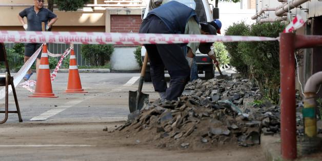 13일 오후 경북 경주시 성건동의 한 아파트에서 관계자들이 전날 발생한 지진의 영향으로 주차장에 떨어진 기와를 치우고 있다