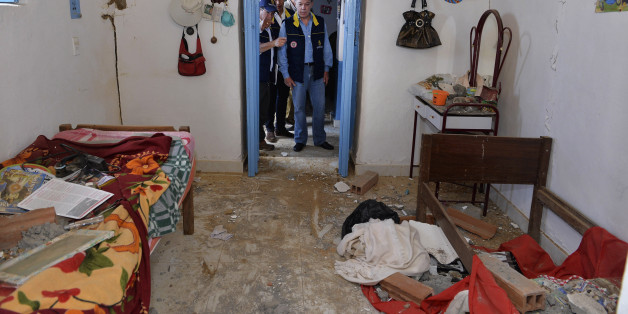 Colombia's President Juan Manuel Santos (C) inspects a house partially damaged by an earthquake in Betulia, Santander province March 11, 2015. A 6.2 magnitude earthquake hit Colombia on Tuesday, shaking buildings in several cities including the capital, Bogota, where residents poured into the streets in panic, but there were no reports of serious injuries or significant damage. The quake's epicentre was located near the eastern city of Bucaramanga, about 272 kilometres (169 miles) northeast of B