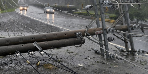 Cars drive past collapsed power lines, that partially block the road, as super typhoon Meranti skirts Pingtung county in southern Taiwan on September 14, 2016.Parts of Taiwan were brought to a standstill on September 14 as the strongest typhoon of the year skirted past the island's southern tip, knocking out power for more than 180,000 households.  / AFP / SAM YEH        (Photo credit should read SAM YEH/AFP/Getty Images)