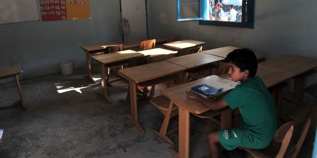 A child sits in a classroom in the refugee camp of Lagadikia, some 40km North of Thessaloniki, during the visit of UN high commissioner for refugees Filippo Grandi on August 25, 2016. More than 58,000 refugees and migrants are stranded in Greece with most of them living in refugee camps, while some 8,000 live in UNHCR arranged shelters, houses or hotels. / AFP / Sakis Mitrolidis        (Photo credit should read SAKIS MITROLIDIS/AFP/Getty Images)