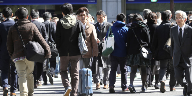 People cross a street in Tokyo, Friday, Feb. 26, 2016. The results of the 2015 census released Friday show the population dropped by 947,000 people in the last five years, the first decline since the count started in 1920. Japan's population stood at 127.1 million last fall, down 0.7 percent from 128.1 million in 2010. (AP Photo/Koji Sasahara)