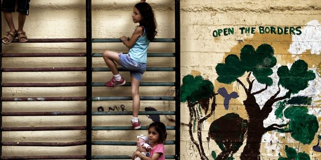 Children play in the courtyard of an abandoned school used by volunteers for hosting Syrian and Afghan refugees in Athens on July 1, 2016. Some 250 people live in self-management in the school of Athens city center, closed for three years. The families occupy three floors of the building, and twenty classrooms, where a tense sheets forest delineate areas of life and protect privacy. The squat was established in mid-March, when the sudden closure of their borders with the countries north of Greece makes it a trap for those who relied only cross to reach Germany or Sweden. Almost all e now living in dozens of camps set up in haste by the government. Some rent rooms. The others are squat. The government estimates about 1,500 the number of people living well into 'outdoor hospitality structures.' / AFP / ARIS MESSINIS        (Photo credit should read ARIS MESSINIS/AFP/Getty Images)