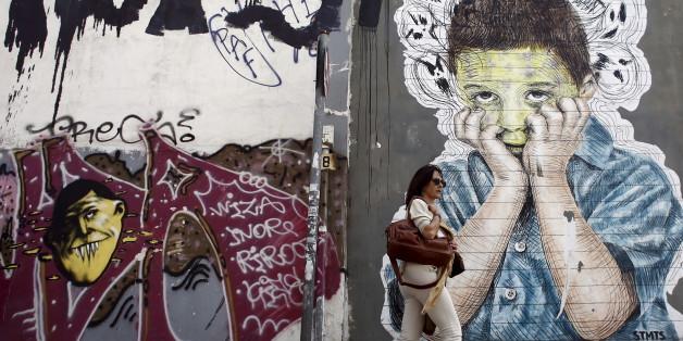 A pedestrian walks past a graffiti in central Athens, April 26, 2015. REUTERS/Kostas Tsironis
