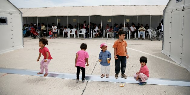 Children play as refugees and migrants wait to take part in a pre-registration process that gives them access to the asylum procedure, at the premises of the disused Hellenikon airport, in Athens, Greece, June 13, 2016. REUTERS/Alkis Konstantinidis