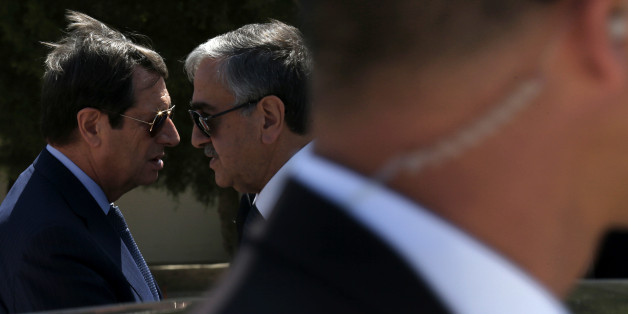 Cypriot President Nicos Anastasiades, left, and breakaway Turkish Cypriot leader Mustafa Akinci, right, talk as a guard stands in front of a car after their meeting aimed at reunifying the ethnically divided island, at the disused Nicosia airport inside a United Nations controlled buffer zone on Wednesday, Sept. 14, 2016. The rival leaders of ethnically split Cyprus say they will meet with the U.N. Chief later this month to take stock of ongoing reunification talks and ask him to step up his personal involvement in the months ahead. (AP Photo/Petros Karadjias)