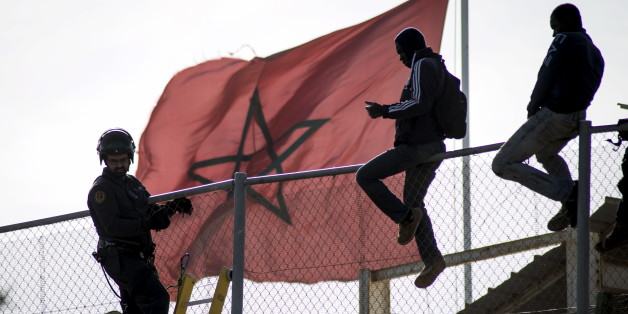 African migrants sit on top of a border fence during an attempt to cross into Spanish territories, between Morocco and Spain's north African enclave of Melilla, November 21, 2015. REUTERS/Jesus Blasco de Avellaneda      TPX IMAGES OF THE DAY