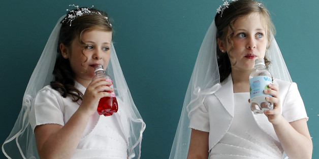 Twin sisters Aine (L) and Emer Quinn drink from bottles in the local parish hall after making their First Holy Communion in St. Mary's Roman Catholic Church, Cushendall, in this photo taken June 5, 2010. The reverence with which the Irish hold the Catholic Church had begun to fade even before the abuse scandals of recent years. As the economy boomed in the 1990s and 2000s, churches emptied. The abuse revelations have further undermined the Church's authority and fractured trust, alienating commi