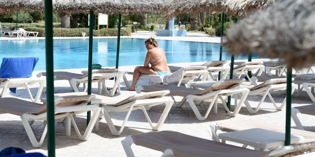 A tourist sits on a sunbed next to a hotel pool on the Tunisian resort island of Djerba on May 26, 2016. Before the 2011 revolution, the annual number of visitors in Tunisia reached nearly seven million, with tourism accounting for some 7% of the gross domestic product (GDP). After years of degradation due to instability following the country's uprising, attendance fell by half after the 2015 attacks against the Bardo Museum in Tunis (March) and Sousse hotel (June), which resulted in 60 dead including 59 foreign tourists.   / AFP / FETHI BELAID / TO GO WITH AFP STORY MOUNIR SOUISSI        (Photo credit should read FETHI BELAID/AFP/Getty Images)