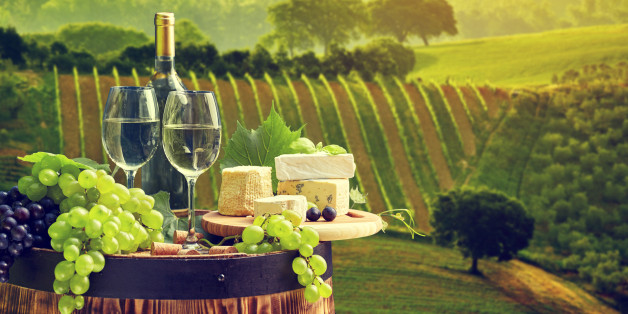 White wine bottle and wine glass on wodden barrel. Beautiful Tuscany background