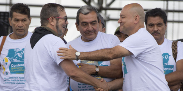 Rodrigo Londono, the top leader of the Revolutionary Armed Forces of Colombia, FARC, also known as Timoleon Jimenez, second from left, is greeted by rebel leaders Carlos Antonio Lozada, and Mauricio Jaramillo, center, after his speech to inaugurate the group's 10th conference in Yari Plains, southern Colombia, Saturday, Sept. 17, 2016. FARC leaders and guerrilla delegates kicked off their last conference as a rebel army as they look to transition into a political movement following the signing o