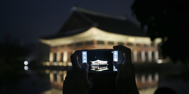 A visitor takes a photograph of Gyeonghoeru pavilion, a part of Gyeongbok palace, during the evening in central Seoul May 23, 2013. Gyeongbok Palace offered late-night admissions to the public from Wednesday until Sunday, The Cultural Heritage Administration said.   REUTERS/Kim Hong-Ji (SOUTH KOREA - Tags: TRAVEL)