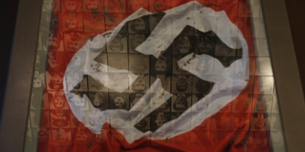 In this photo taken Saturday, March 21, 2015, a Nazi flag is displayed at the Holocaust Museum in the town of Kalavryta, western Greece, as portraits of victims are reflected in a glass pane. It was 1943 and the Nazis were deporting Greece's Jews to death camps in Poland. Hitler's genocidal accountants reserved a chilling twist: The Jews had to pay their train fare. The bill for 58,585 Jews sent to Auschwitz and other camps exceeded 2 million Reichsmark — more than 25 million euros ($27 million) in today's money. For decades, this was a forgotten footnote among all of the greater horrors of the Holocaust. Today it is returning to the fore amid the increasingly bitter row between Athens and Berlin over the Greek financial bailout. (AP Photo/Petros Giannakouris)