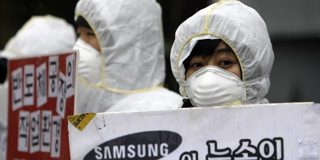 In this photo taken on March 25, 2010, South Korean activists, wearing protective clothing, participate in a rally near the Samsung semiconductor factory in Yongin, south of Seoul, South Korea, Thursday, July 15, 2010. Samsung Electronics said Thursday, July 15, 2010,  it has commissioned an independent health and safety review of its semiconductor factories in South Korea after employee illnesses and deaths raised fears of cancer risks.  (AP Photo/ Lee Jin-man)