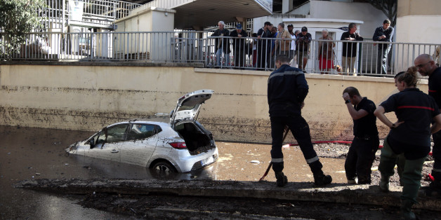French fireman work near an abandoned car stuck in muddy waters near an underpass after flooding caused by torrential rain in Cannes, France, October 4, 2015. Flooding along part of the French Riviera has killed at least 16 people, officials now said Sunday. The downpour hit the Alpes-Maritimes region, which lies at the eastern end of France's Mediterranean coast and borders Italy, on Saturday evening. REUTERS/Eric Gaillard ATTENTION EDITORS FRENCH LAW FORBIDS THE PUBLICATION OF AUTOMOBILE REGISTRATION PLATES IN PUBLICATIONS WITHIN FRANCE