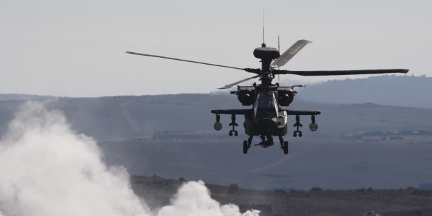 An AH-64 Apache helicopter flies over smoke while taking part in Exercise Trident Juncture 2015, NATO's largest joint and combined military exercise in more than a decade, at the San Gregorio training grounds outside Zaragoza, Spain, November 4, 2015. Some 36.000 personnel from more than 35 nations, including all NATO Allies  will have participated in Exercise Trident Juncture 2015 which began on 21 October, in Italy, Portugal and Spain, including their adjacent waters and airspace and runs till November 6.  REUTERS/Paul Hanna