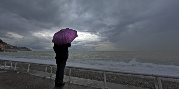 A woman protects herself under an umbrella during an autumn day on the Promenade Des Anglais in Nice while heavy rain and storm hit the French Riviera November 5, 2014.  REUTERS/Eric Gaillard (FRANCE - Tags: SOCIETY ENVIRONMENT TPX IMAGES OF THE DAY)