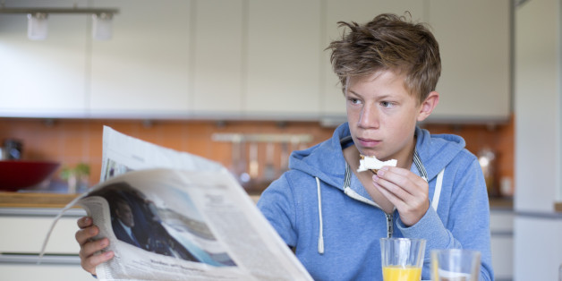 DUELMEN, GERMANY - AUGUST 13: Fourteen-year-old boy reading the newspaper at the breakfast table on August 13, 2014, in Duelmen, Germany.  Photo by Ute Grabowsky/Photothek via Getty Images)***Local Caption***