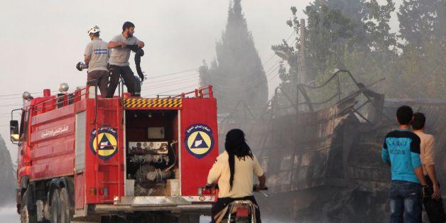 Des membres de la sécurité civile luttent contre les flammes qui dévorent un convoi d'aide humanitaire près de la ville d'Alep, dans le nord de la Syrie