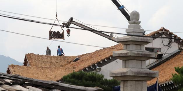 21일 오후 경북 경주시 황남동의 한 식당에서 인부들이 지진 피해를 입은 기와를 교체하고 있다.