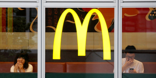 Customers using mobile phones, are seen through the windows of a McDonald's store in Tokyo, Japan July 22, 2016. REUTERS/Toru Hanai/File Photo