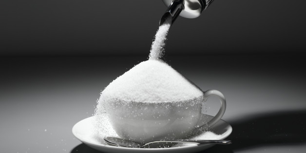 Sugar being poured into tea cup, close-up