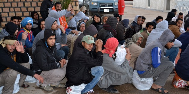 Egyptian workers wait after having crossing the Tunisian border at the Ras Jdir border crossing between Libya and Tunisia, Friday, Feb. 20, 2015.  A group of almost 200 Egyptians have crossed into Tunisia from Libya, the first of thousands expected to flee the turmoil in the country. The execution of 21 Egyptian Christians by extremists and retaliatory Egyptian airstrikes has prompted many Egyptians to want to leave Libya. Authorities said 192 Egyptians went through the Ras Jdir border crossing Friday and headed to the Djerba airport where they will fly back to Cairo. (AP Photo/Ali Manssour)