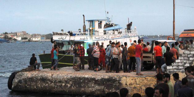 Des personnes rassemblées sur l'embarcadère du port de Rosette après le naufrage d'un bateau de migrants, le 21 septembre 2016 en Egypte