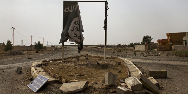 In this Sunday, August 28, 2016 photo, a partially destroyed Islamic State group banner hangs at the entrance to Qayara, Iraq. The skies above Qayara are black with the smoke from more than a dozen oil wells set alight by Islamic State group fighters attempting to obstruct airstrikes as Iraqi forces pushed into the the town on bank of the Tigris last week and took control of the entire area Thursday. (AP Photo/Susannah George)