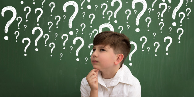 Little boy thinking surrounded question marks on chalkboard