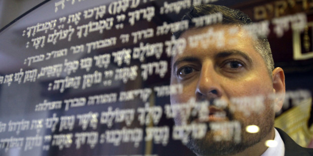 In this picture taken Friday, May 30, 2014, Csanad Szegedi waits in a Budapest Synagogue. Szegedi was a rising star of Hungary's far-right, dumped by his party after he admitted he was a Jew. Two years later, Csanad Szegedi has completed an astonishing transformation: He goes to synagogue, eats Kosher food and has adopted the Hebrew name Dovid. (AP Photo/Peter Kohalmi)