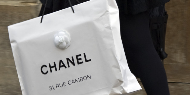 A woman walks with a shopping bag from fashion house Chanel in central Paris October 13, 2008.   REUTERS/Charles Platiau   (FRANCE)