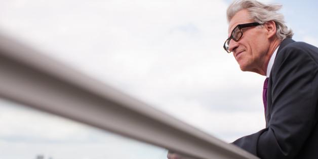 Businessman leaning on balcony railing
