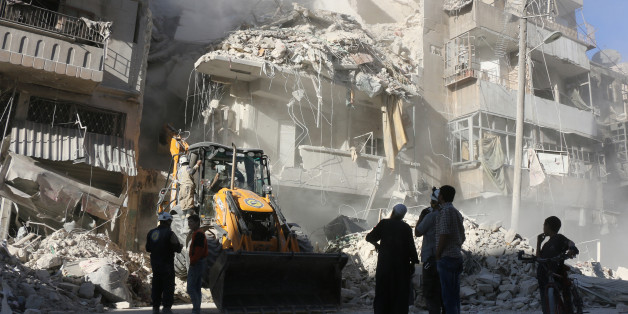 Civilians watch as a tractor clears the rubble following Syrian government forces airstrikes in the rebel held neighbourhood of Tariq a-Bab in Aleppo on September 24, 2016. Residents in Syria's battleground city of Aleppo cowered indoors as fierce air strikes toppled buildings and killed at least 52 civilians, after diplomatic efforts to revive a ceasefire failed. / AFP / THAER MOHAMMED        (Photo credit should read THAER MOHAMMED/AFP/Getty Images)