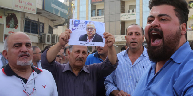 Demonstrators shout slogans during a demonstration in the town of Fuheis, 20km northwest of the capital Amman on September 25, 2016, denouncing the killing of prominent Jordanian writer Nahed Hattar (portrait).Hattar was shot dead on the steps of a court where he was facing charges for sharing an anti-Islam cartoon online, in an attack condemned as 'heinous'.Nahed, a 56-year-old Christian, was struck by three bullets before the alleged assassin was arrested at the scene of the shooting in Amman'