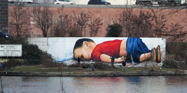 A graffiti by artists Justus Becker and Oguz Sen depicts the drowned Syrian refugee boy Alan Kurdi (initially reported as Aylan Kurdi) at the harbor in Frankfurt am Main, Germany, on March 10, 2016. / AFP / DANIEL ROLAND / RESTRICTED TO EDITORIAL USE - MANDATORY MENTION OF THE ARTIST UPON PUBLICATION - TO ILLUSTRATE THE EVENT AS SPECIFIED IN THE CAPTION        (Photo credit should read DANIEL ROLAND/AFP/Getty Images)