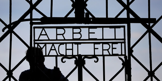 """A blacksmith prepares a replica of the Dachau Nazi concentration camp gate, with the writing """"Arbeit macht frei"""" (Work Sets you Free) at the main entrance of the memorial in Dachau, Germany, Wednesday, April 29, 2015. The gate was stolen in November 2014. (AP Photo/Matthias Schrader)"""