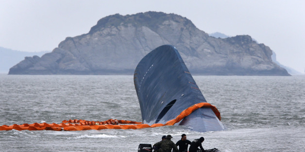 """A vessel involved in salvage operations passes near the upturned South Korean ferry """"Sewol"""" in the sea off Jindo April 17, 2014. Rescuers were hammering on the upturned hull of a capsized South Korea ferry on Thursday hoping for a response from hundreds of people, mostly teenage schoolchildren, believed trapped after the vessel started sinking more than 24 hours previously. REUTERS/Kim Kyung-Hoon  (SOUTH KOREA - Tags: DISASTER MARITIME TPX IMAGES OF THE DAY)"""