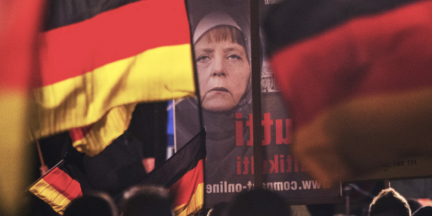 A banner depicting a manipulated image of German Chancellor Angela Merkel is carried by a protester during a demonstration initiated by the Alternative for Germany (AfD) party against what they call the uncontrolled immigration and asylum abuse in Erfurt, central Germany, Wednesday, Nov. 18, 2015. (AP Photo/Jens Meyer)
