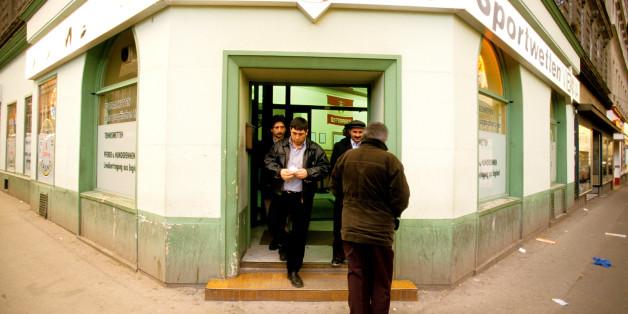 Migranten verlassen ein Wettbüro in Wien