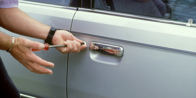 close-up of mans hands using screwdriver to break into car