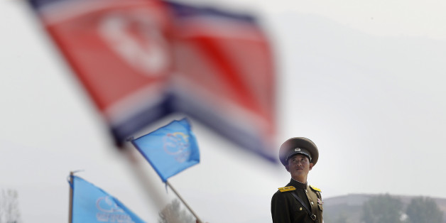 In this Sept. 24, 2016 file photo, a North Korean military soldier stands guard as North Koreans wave flags and cheer during an aerial display, in Wonsan, North Korea. North Korea on Saturday opened an air festival featuring sky diving, demonstrations by its air force and lots of beer to promote a newly renovated and upgraded commercial airport in the coastal city of Wonsan that it hopes will draw for foreign tourists. (AP Photo/Wong Maye-E, File)