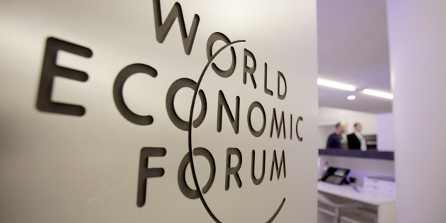People walk by a sign in the meeting center at the World Economic Forum in Davos, Switzerland on Tuesday, Jan. 25, 2011. On the eve of the annual World Economic Forum, new reports are being released that will examine whether there is optimism about the global economy in the coming months and, perhaps more importantly, if the levels of trust in business and government are on the rebound. (AP Photo/Virginia Mayo)