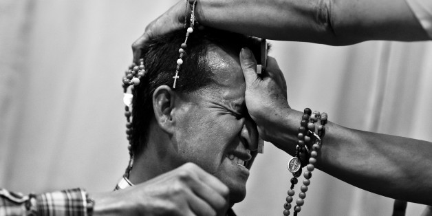 BOGOTA, COLOMBIA - MARCH 10:  A Colombian pastor, pressing a crucifix on a believer's head, attempts to evict a supposed demon during the exorcism ritual performed at a house church on March 10, 2016 in Bogota, Colombia. Hundreds of Christian belivers, joined in nameless groups, gather every week in unmarked home churches dispersed in the city outskirts, to carry out prayers of liberation and exorcism. (Photo by Jan Sochor/Latincontent/Getty Images)