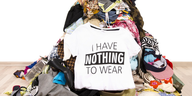 Big pile of clothes thrown on the ground with a t-shirt saying nothing to wear. Close up on a untidy cluttered wardrobe with colorful clothes and accessories,